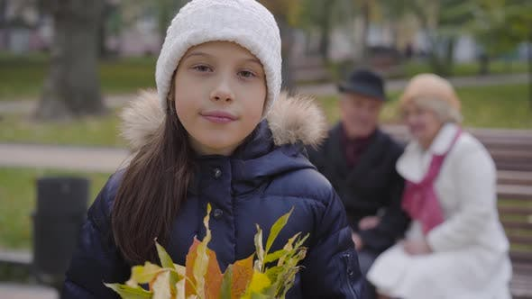 Thumbnail for Smiling Caucasian Girl in White Hat Holding a Bunch of Yellow Leaves and Looking at the Camera