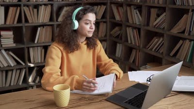 Hispanic Girl Wearing Headphones Distance Learning on Laptop By Videoconference