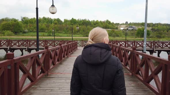 Thumbnail for Blonde Girl Walking on the Bridge and Looks Into the Camera.