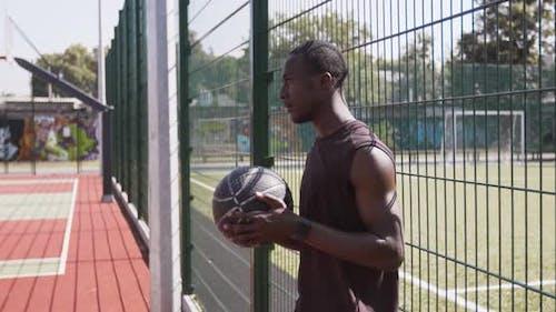 Nahaufnahme eines nachdenklichen afroamerikanischen Basketballspielers, der mit Ball beim Outdoor-Streetball steht