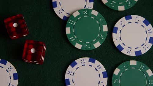 Rotating shot of poker cards and poker chips on a green felt surface - POKER 040