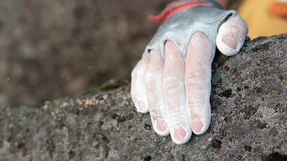 Closeup of a Rock Climber's Hands in Chalk Grabbing a Rock Ledge
