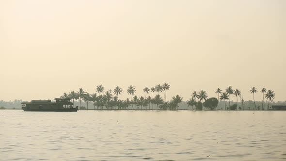 Landscape view of a houseboat floating on a river, Kerala Backwaters, India