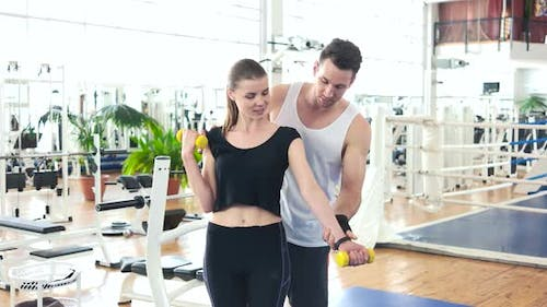 Male Instructor Helps To Girl Lifting Dumbbell.