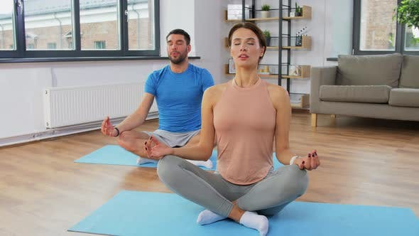 Happy Couple Meditating in Yoga Lotus Pose at Home