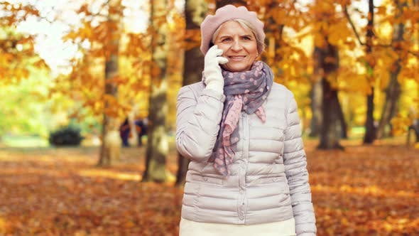 Thumbnail for Senior Woman Calling on Smartphone at Autumn Park