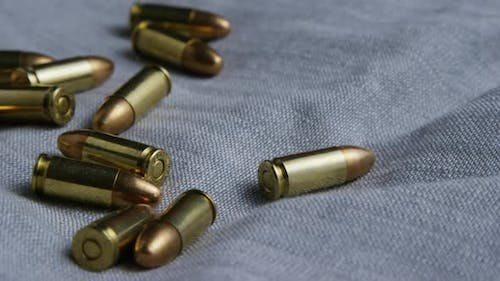 Cinematic rotating shot of bullets on a fabric surface - BULLETS 084