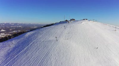 Old Ski Station on a Snowy Mountain Slope with a Lot of People on Skis and Snowboards