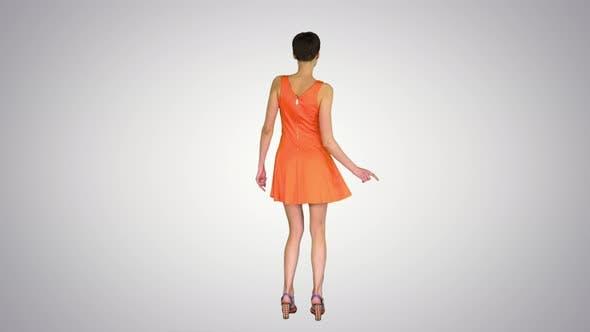 Thumbnail for Girl Dancing in Orange SunDress on Gradient Background.