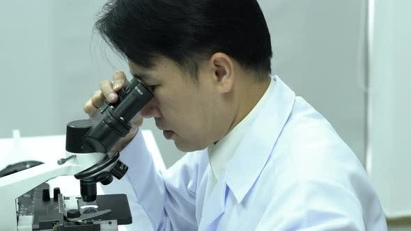 Man looking microscope in laboratory
