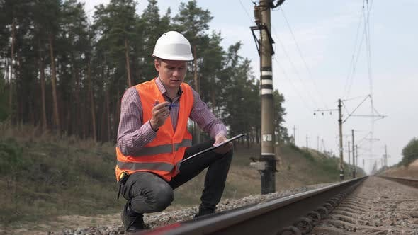 Railway Engineer Counts the Number of Sleepers and Writes in a Notebook