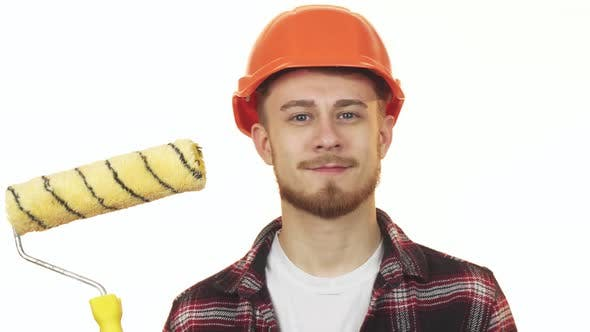 Thumbnail for Happy Young Male Builder Holding Paint Roller Showing Thumbs Up