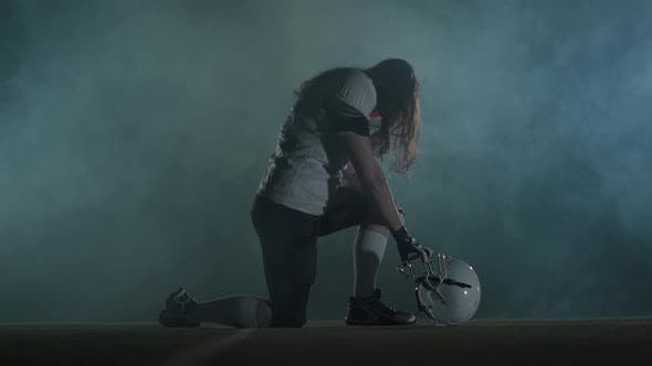 Thumbnail for American Football Sportsman Player with Long Hair in Football Helmet Standing on One Knee on the