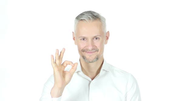 Cover Image for Ok Sign By Grey Haired Businessman , White Background