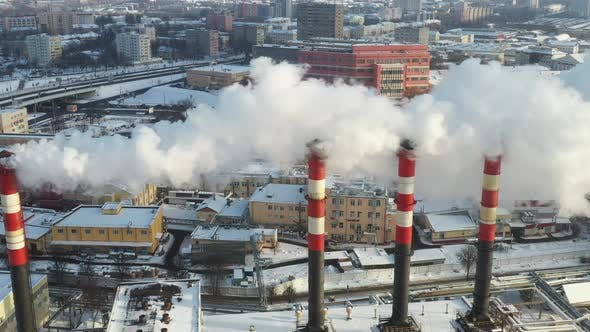 In the winter city, the factory's chimneys are smoking. The concept of air pollution.