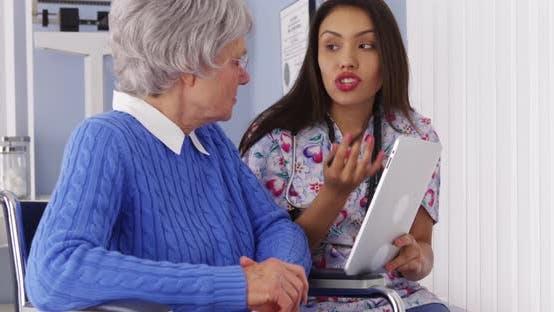 Hispanische Betreuer im Gespräch mit Tablette mit älteren Patienten