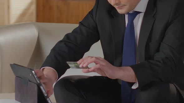 Thumbnail for Man in Business Suit Typing Credit Card Number on Tablet Screen, Paying Bills