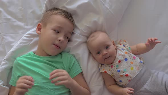 Thumbnail for A Brother and a Baby Sister Lying on a Bed Close To Each Other