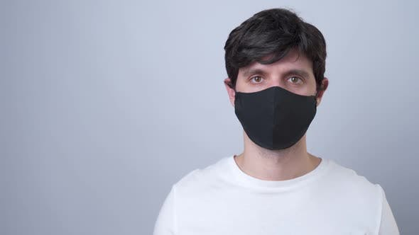 Thumbnail for Man in a Black Medical Mask, Isolated on a Gray Background