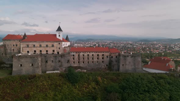 Aerial View of Medieval Castle on Mountain in Small European City at Cloudy Autumn Day