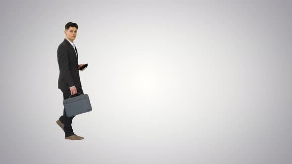 Thumbnail for Handsome Suspicious Businessman Walking by With a Phone