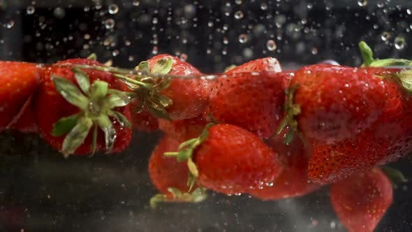 Cover Image for Vibrant strawberries falling and floating in aquarium full with water