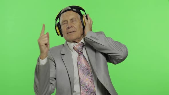 Thumbnail for Funny elderly senior businessman in suit listens to music in headphones and dances. Chroma key