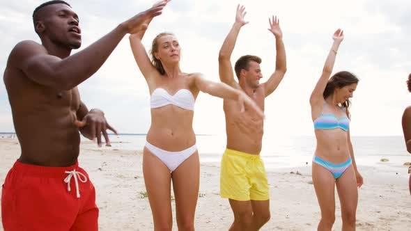 Счастливые друзья танцуют в летний пляж вечеринка