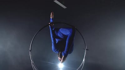 Gymnastics Performance in the Studio By a Young Woman in Blue Costume in a Hoop