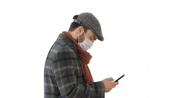 Thumbnail for Stylish Man in Medical Mask Walking and Using Smart Phone on White Background