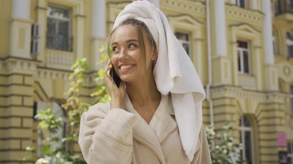 Thumbnail for Portrait of Cute Smiling Jou Young Woman in Bathrobe with Towel on Head Talking By Cellphone on the