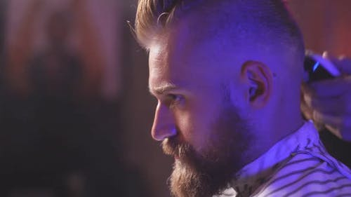 Handsome Satisfied Bearded Caucasian Guy Getting Trendy Haircut, Barber Serving Client