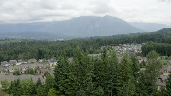Cover Image for Rising Above Aerial Revealing Nature Landscape Of Mountains And Tree Lined Homes