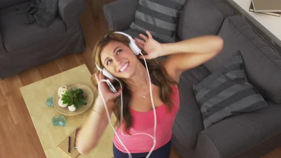 Happy young woman listening to music on headphones