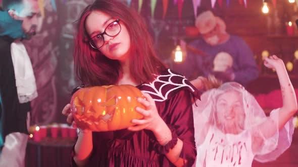 Teenager-Mädchen tanzt in Zeitlupe mit einem geschnitzten Kürbis in Ihre Hand auf einer Halloween-Party
