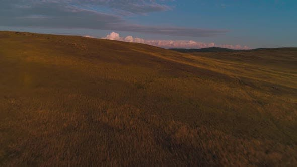 Aerial Field of Dry Yellow Grass. Steppe on Olkhon Island. Lake Baikal, Russia. Drone Footage Hills