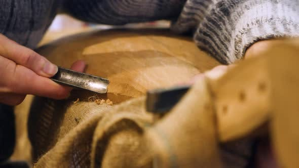 Wooden Workwhop. A Man Carves a Wood. The Carpenter Works in a Studio. An Engineer Provides a Tree