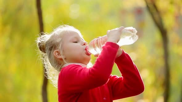 Little girl drinks clean water in the outdoors. Little girl drinks clean water in autumn Park.