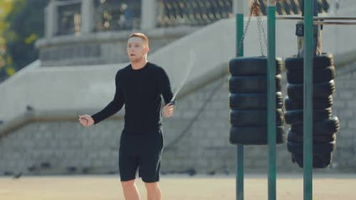 Young Guy springt professionell Seil, das sich im Sommer auf dem Sportplatz aufwärmt