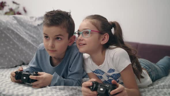 Thumbnail for Happy Kids Playing Video Game with Joystick at Home. Friends Play Game Console