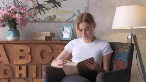 A young girl of 20-25 years old is reading a book in a bright room; She enjoys reading