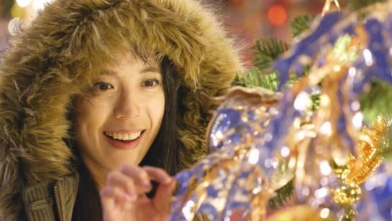 Thumbnail for Young Woman looking at the christmas tree decoration