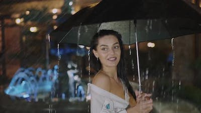 Wet Girl Turning Around with Umbrella and Looks at Camera