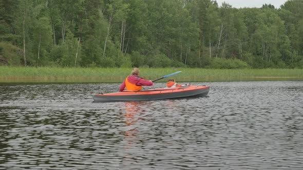 Thumbnail for Woman Rows Small Kayak with Kid Sailing Along Large Lake