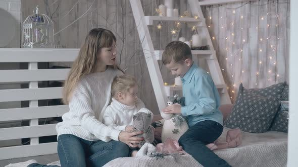 Thumbnail for Blond Mother Son and Daughter Play with Stuffed Soft Toys