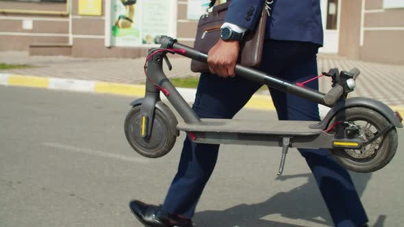 Businessman Carrying Folded Electric Scooter Along Street