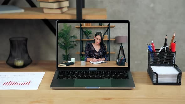 Laptop Standing on Table Display with Businesswoman in Office Writes in Notebook