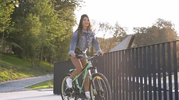 Thumbnail for Adorable Smiling Hot Girl in Jeans Clothes Riding on Bicycle Near Metal Fence