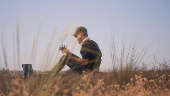 Musician Plays Bass Guitar Outdoors
