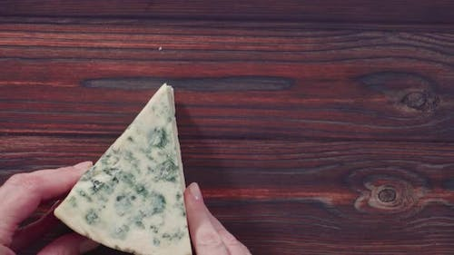 Flat lay. Large wedge of blue cheese on a dark wooden background.